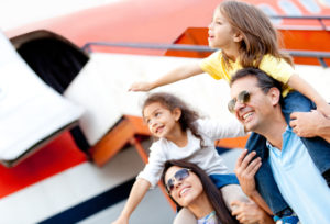 Excited family with arms up traveling by airplane