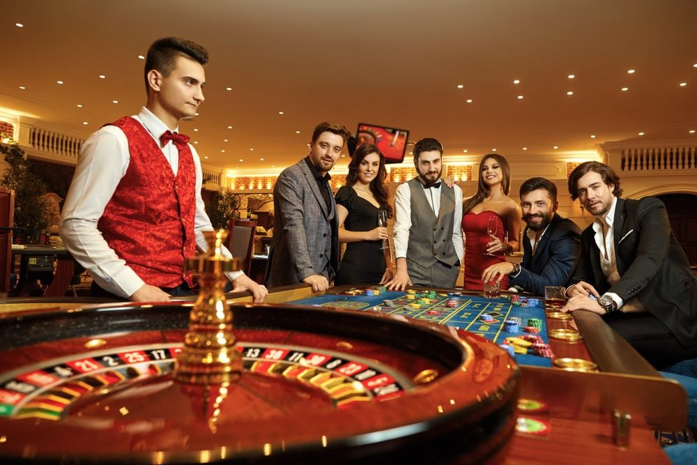 happy group of friends making bets at the roulette table in a casino