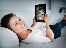 woman relaxing on a couch and playing online games on her tablet